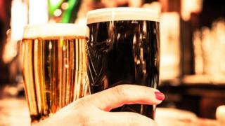 Woman's hand holding pint of stout