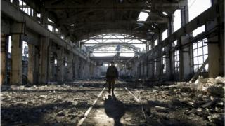 Український військовий йде через зруйнований внаслідок боїв цех в Авдіївці, 31 березня 2017 року.