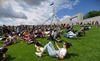 Hundreds of people are pictured rolling down the lawns of Parliament House in Canberra, Australia, on 17 December 2016.