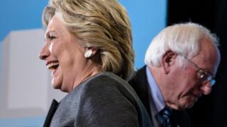 Hillary Clinton and Bernie Sanders face different directions at a 2016 campaign event.