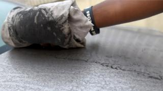 An attendant wipes clean black soot covering a car