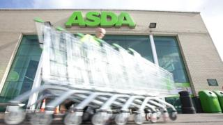 Asda employee collects trolleys