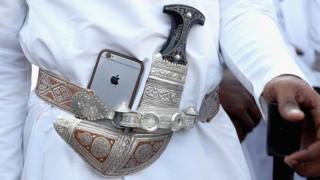 Un bailarín pone su iPhone de Apple junto a su tradicional daga omaní durante una ceremonia de bienvenida en Muscat, Omán (5 de noviembre de 2016).