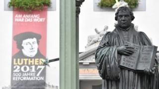 A statue of German Church reformer Martin Luther alongside a poster in the main square in Wittenberg, eastern Germany, 31 October 2017