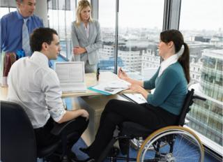 Office meeting with woman sitting in a wheelchair