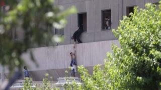 ภาพที่ดูเหมือนเด็ก กำลังถูกหย่อนตัวลงจากหน้าต่างอาคารรัฐสภาอิหร่าน