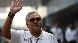 Force India team principal Vijay Mallya waves in the paddock during the third practice session of the Indian F1 Grand Prix at the Buddh International Circuit in Greater Noida