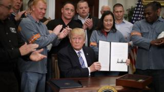 President Donald Trump holds up a piece of paper with his signature while surrounded by steel workers in uniform