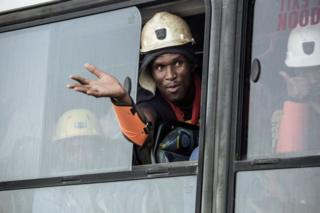 A rescued miner gestures out a bus window carrying some of the hundreds of miners rescued from the Beatrix gold mine shaft number 3 where nearly 1,000 miners were trapped underground following a power outage, in Theunissen on February 2, 2018. Hundreds of gold miners among almost a thousand trapped underground for more than a day in South Africa following a power-cut resurfaced on February 2, mining company Sibanye Gold said, as a rescue effort moved into full swing.