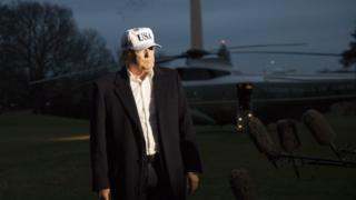 President Trump, wearing a USA cap and white shirt with a a jacket, speaks to media with helicopter in background