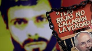 A man holds a sign with a portrait of opposition leader Antonio Ledezma in front of a wall with a portrait of opposition leader Leopoldo Lopez during a news conference