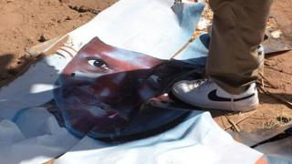 A supporter of the opposition foots a poster showing Jammeh's face on close-up