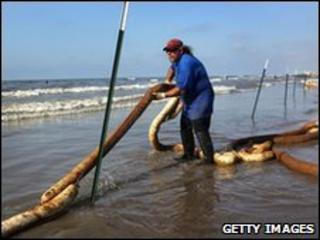 A BP clean-up worker stretches an oil-soaked boom along a beach on Elmer's Island, Louisiana, 23 May