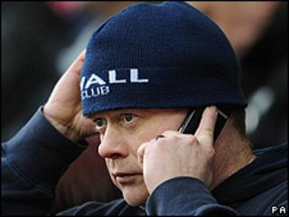 Millwall football fan using mobile phone