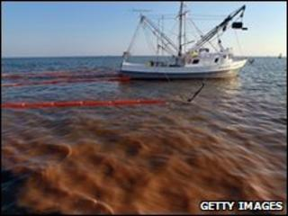 A shrimp boat collects oil with booms off Louisiana, 5 May