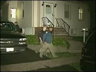 Law enforcement agents outside one of the arrested men's homes