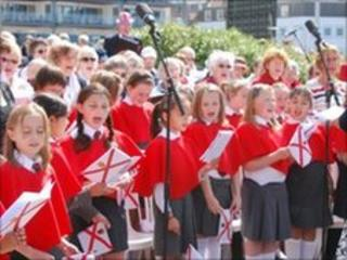 Schoolchildren singing An Island Home on Liberation Day
