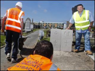 Community payback supervisor Sid Giles [R] near the grave