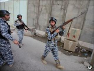 Iraqi policemen prepare to secure the scene of bombings in central Baghdad, Sunday, June 13, 2010.