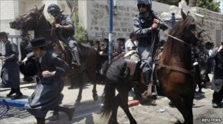 Mounted Israeli police officers try to disperse ultra-Orthodox Jews during a protest in Jaffa