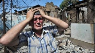 An ethnic Uzbek besides the wreckage of his burned out home in Osh