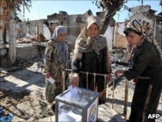 Ethnic Uzbek women vote in Osh, amid the devastation of their community