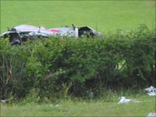 The remanins of the crashed Subaru car can be seen behind a hedge