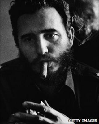 Headshot portrait of Cuban premier Fidel Castro lighting a cigar, New York City, 1959