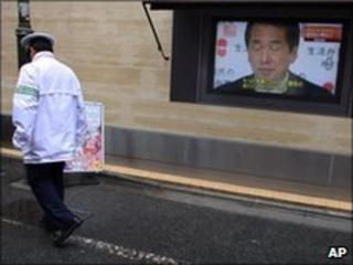 A man walks past a TV screen showing PM Naoto Kan in Tokyo on 12 July 2010