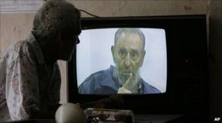 Cuban man watches Castro on TV