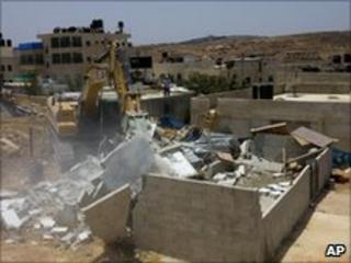 A bulldozer demolishes a house in the east Jerusalem neighbourhood of Beit Hanina, Tuesday 13 July