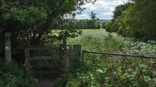 A gate and footpath through fields on the Gloucestershire Way near Winchcombe, Gloucestershire