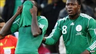 Nigeria's midfielder Sani Kaita (L) hides his face after being handed a red card