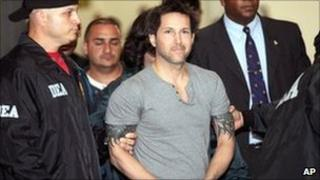 Jose Figueroa Agosto is escorted by US agents in San Juan. Photo: 17 July 2010