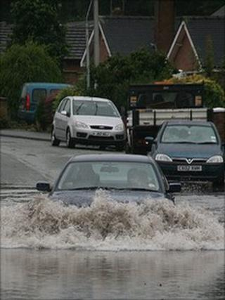 A car driving through a flooded section of road in Wrexham