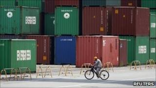 A man walks past a pile of containers at a container yard near a port in Tokyo