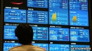 man looking at stock exchange board