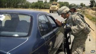 A US soldier talks to a driver during a search for the two missing US Navy personnel in Logar province on 25 July 2010