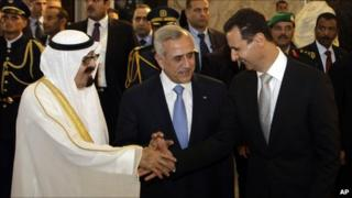 King Abdullah shakes hands with Bashar al-Assad in front of Michel Suleiman (30 July 2010)