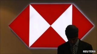 A worker is silhouetted against an illuminated sign in a branch of HSBC in the City of London