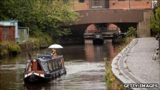 A narrow boat cruises through the rain at Wigan Pier on the Leeds-Liverpool Canal