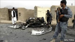 An Afghan policeman keeps watch at the site of a blast in Dand district of Kandahar province