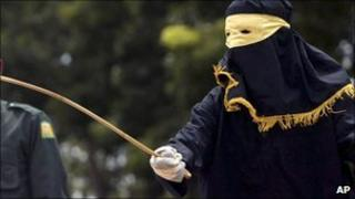 A Sharia law official with a rattan cane in Aceh (June 2010)
