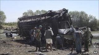 Afghan police inspect the burned tanker in Kunduz