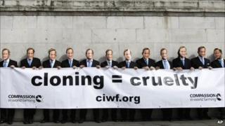 Activists wearing masks of Prime Minister David Cameron