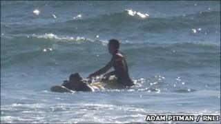 One of Freshwater West's lifeguards helping one of the rip current victims to safety (RNLI/Adam Pitman)