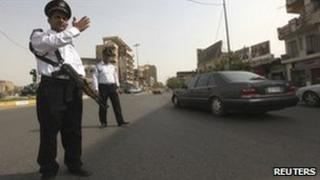 A policeman armed with a Kalashnikov directs traffic in Baghdad, 6 August