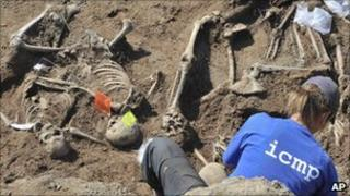 A forensic expert examines the remains of bodies believe to be victims of the Visegrad massacre