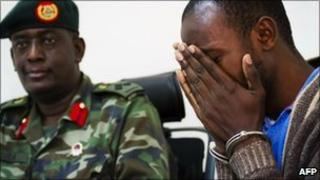 Edris Nsubuga weeps at a press conference given by the Ugandan military on 12 August 12 2010