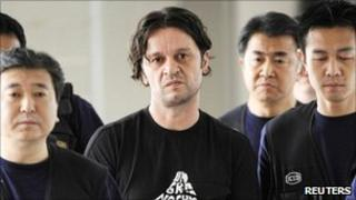 Suspect Rifat Hadziahmetovic (centre) is escorted by Japanese authorities at Narita international airport, east of Tokyo. Photo: August 2010